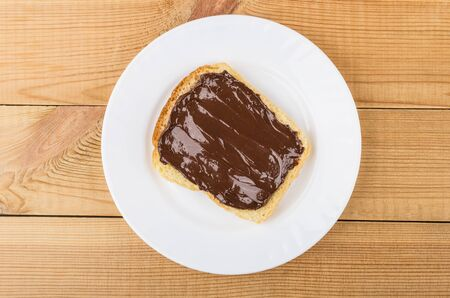 smeared: Sandwich with chocolate cheese in white plate on wooden table. Top view