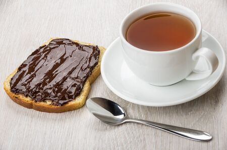 smeared: Sandwich with chocolate cheese, cup of tea and teaspoon on wooden table Stock Photo