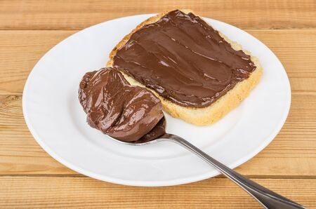 Sandwich and spoon with chocolate cheese in white plate on wooden table