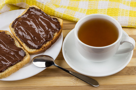 Sandwiches with chocolate cheese and cup of tea on striped table Stock Photo