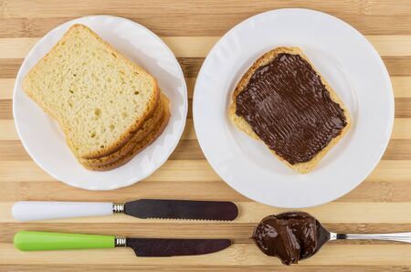 Sandwich and spoon with chocolate cheese, knifes, pieces of bread in white plate on striped table. Top view Stock Photo
