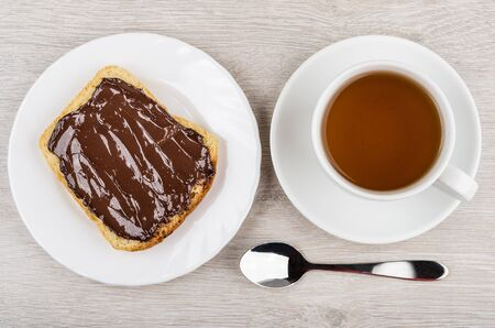 smeared: Sandwich with chocolate cheese in plate, tea and teaspoon on wooden table. Top view