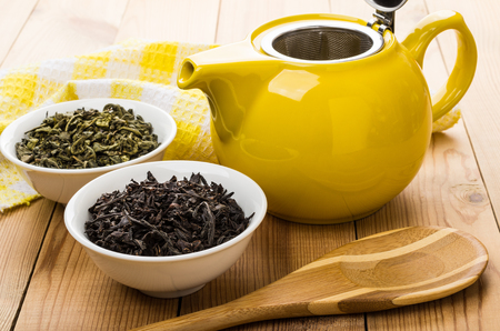 Bowls with dry green and black tea, teapot, spoon on wooden table