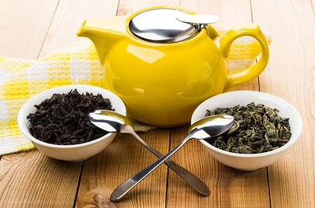 Yellow teapot, bowls with dry green and black tea, teaspoons on wooden table