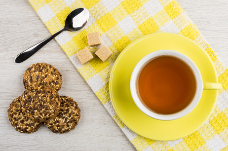 Hot tea and lump sugar on yellow napkin, cookies on wooden table. Top view