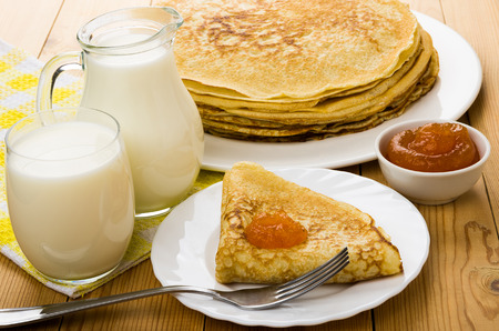 Russian pancakes in dish with peach jam, jug milk and glass on wooden table Reklamní fotografie