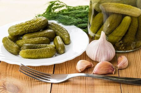 marinated gherkins: Plate with gherkins, fork, garlic and jar with cucumbers on wooden table