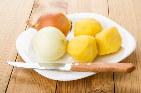 washed: Peeled raw potatoes, onion in plate, kitchen knife on wooden table Foto de archivo