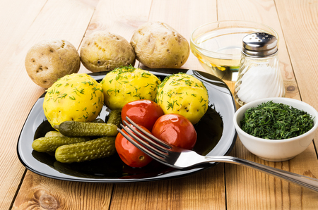 marinated gherkins: Baked potatoes, pickled gherkins and tomatoes, greens, bowl with oil and salt on wooden table Stock Photo