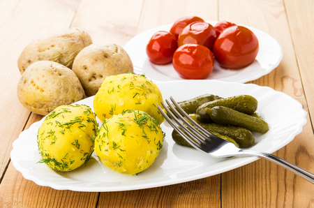 marinated gherkins: Baked potatoes with pickled gherkins on dish, marinated tomatoes in plate on wooden table Stock Photo