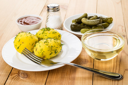 marinated gherkins: Baked potatoes with dill on plate, ketchup, salt, pickled gherkins and vegetable oil on wooden table