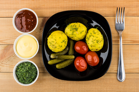 marinated gherkins: Baked potatoes with dill, pickled gherkins and tomatoes, greens, bowls with sauces on wooden table. Top view