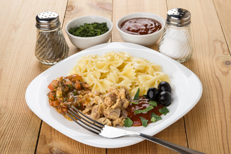 macarrones: Pasta with chicken meat, ketchup, greens, pepper and fork on wooden table Foto de archivo