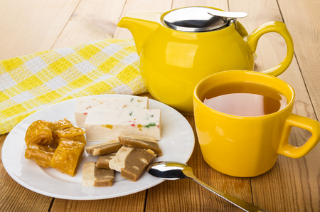 pastila: Oriental sweets in dish, teapot and cup of tea on wooden table