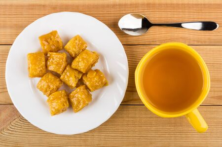 puff: Heap of puffs in sugar syrup in plate and cup of tea on wooden table. Top view