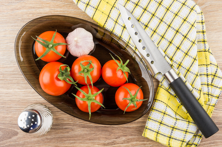 Black dish with red tomatoes and garlic, knife on napkin and salt on wooden table. Top view