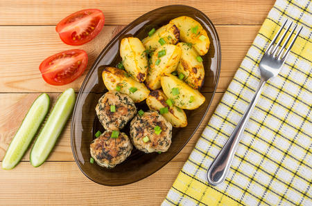 Dish with fried meatballs, baked potatoes, pieces of tomatoes and cucumbers. Top view Stock Photo
