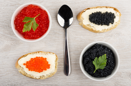 Nachgemachter roter und schwarzer Kaviar in den Schüsseln, Sandwiche mit Butter auf Holztisch. Draufsicht Standard-Bild - 73968385