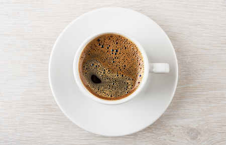 Black hot coffee in cup with saucer on wooden table. Top view