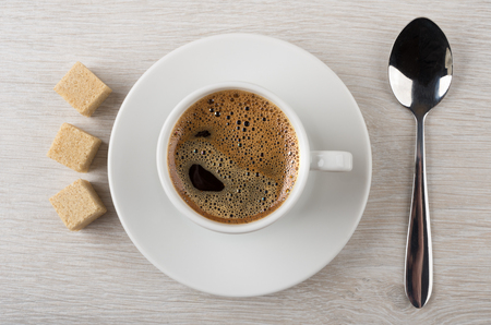 Black hot coffee in cup, brown lumpy sugar and spoon on wooden table. Top view