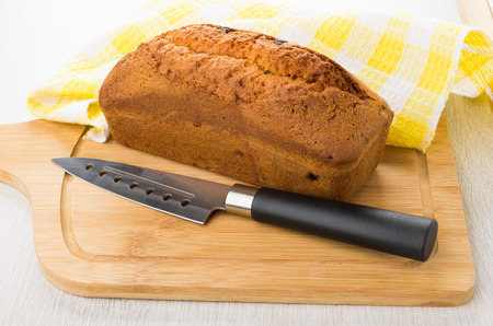 Muffin loaf with raisin and knife on wooden board on table Stock Photo