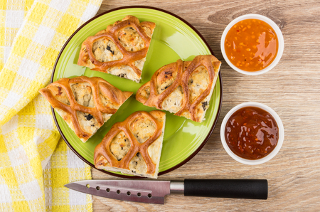 Pieces of chicken pie stuffed in green plate, knife, bowls with sauces on wooden table. Top view Stock Photo