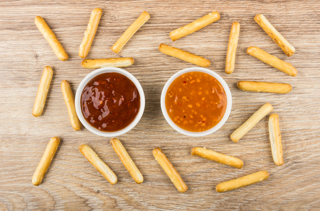 Scattered bread sticks, bowls with sauces on wooden table. Top view