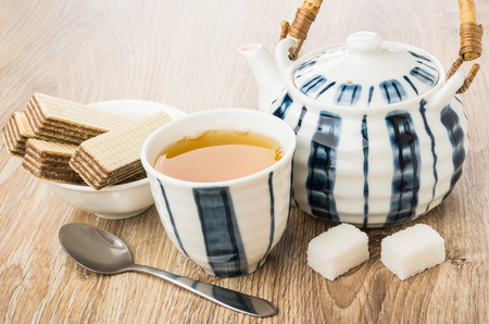 Tea, wafers in bowl, teapot, lumpy sugar and spoon on wooden table Stock Photo