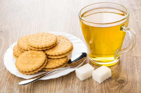 Cup of tea, cookies in plate and lumpy sugar on wooden table