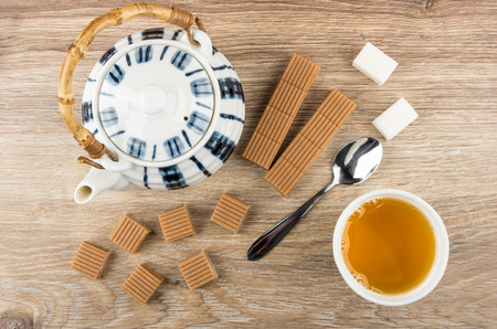 Tea, creamy toffee, teapot, lumpy sugar and spoon on wooden table. Top view