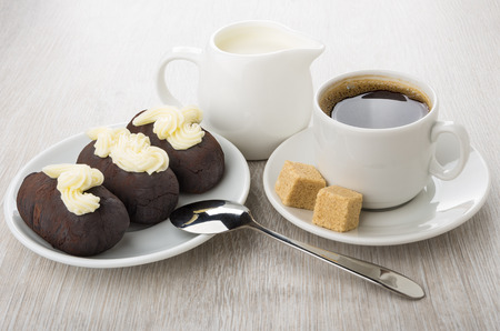 Chocolate biscuit cakes in saucer, jug of milk, black coffee, brown sugar and spoon on wooden table