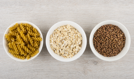 Bowls with pasta, oatmeal and buckwheat - source slow carbs on wooden table. Top view Archivio Fotografico