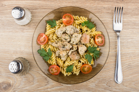 durum: Plate with pasta, chicken meat and tomatoes, salt, pepper and fork on wooden table. Top view