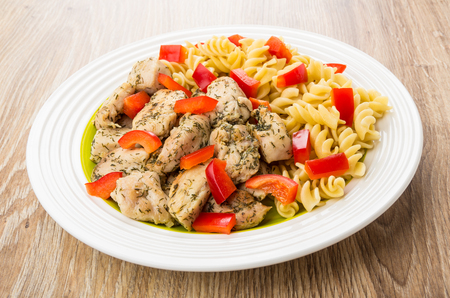 durum: Fried chicken meat with spiral pasta and sweet pepper in plate on wooden table