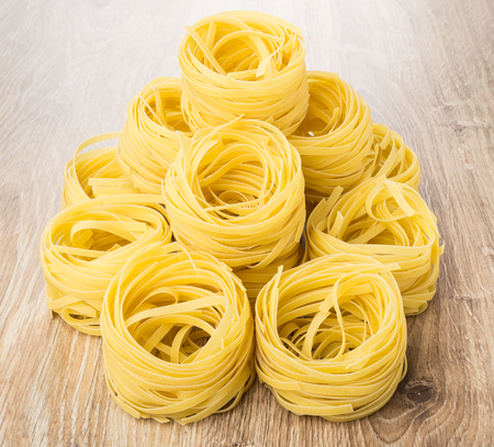 Heap of pasta in form of nest on wooden table