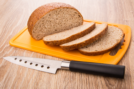 Pieces of bread on plastic cutting board and kitchen knife on wooden table
