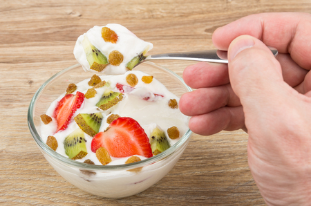 vibrant cottage: Spoon with cottage cheese and fruits in male hand above bowl Stock Photo