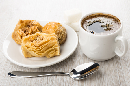 Baklava in white saucer, coffee in cup, sugar and spoon on wooden table