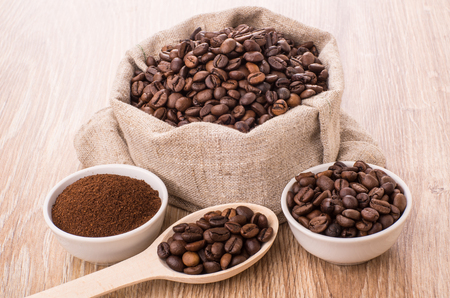 Burlap bag with roasted coffee beans, wooden spoon and bowls on table Stock Photo