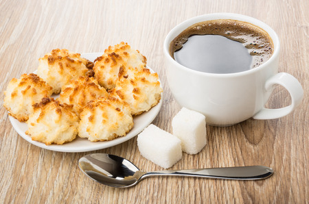 Black coffee, lumpy sugar, spoon and saucer with coconut cookies on wooden table