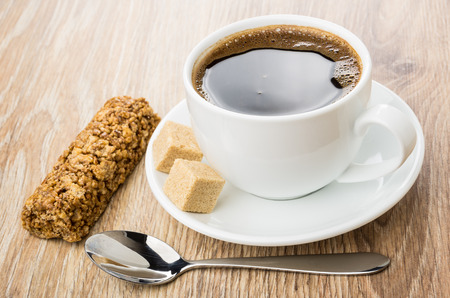 Black coffee, brown lumpy sugar, granola bar and spoon on wooden table Stock Photo