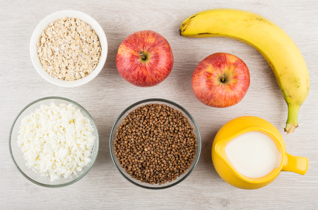Milk, cottage cheese, buckwheat , oatmeal and fruits on wooden table. Top view