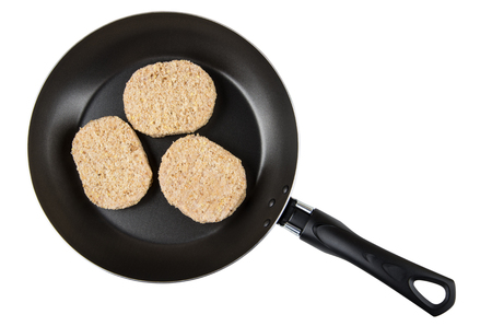 Semi-finished cutlets in frying pan isolated on white background. Top view Stock Photo