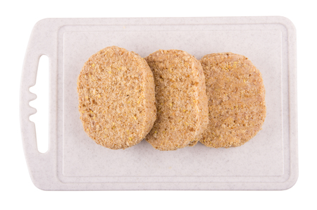 Three raw cutlets on plastic cutting board isolated on white background. Top view Stock Photo