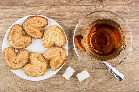 Puff cookies in white plate, cup with tea, lumpy sugar and spoon on wooden table. Top view