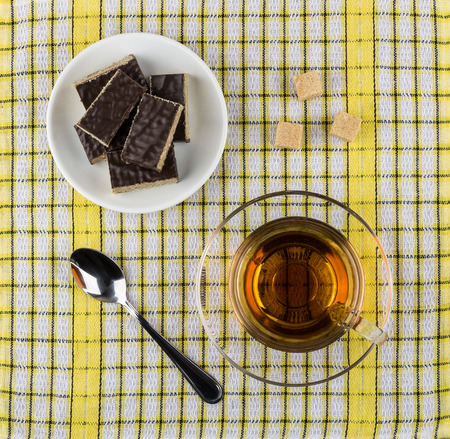 Pieces of chocolate waffle cake in saucer, teaspoon, lumpy sugar and cup of tea on checkered tablecloth. Top view