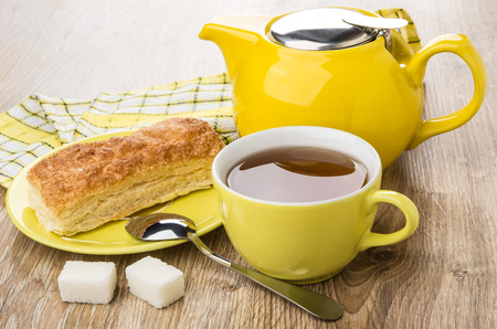 Flaky cookies in saucer, teapot, cup of tea, spoon and lumpy sugar on wooden table