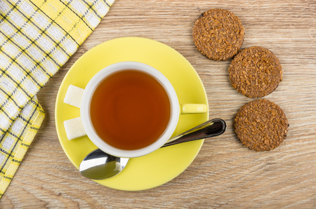 Cup of tea, teaspoon, lumpy sugar on saucer, biscuits and napkin on wooden table. Top view Stock Photo