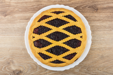 shortbread: Bilberry pie in white dish on wooden table. Top view