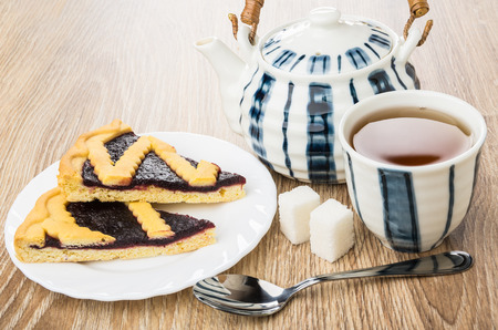 Pieces of bilberry pie in plate, teapot, cup of tea, lumpy sugar and teaspoon on wooden table